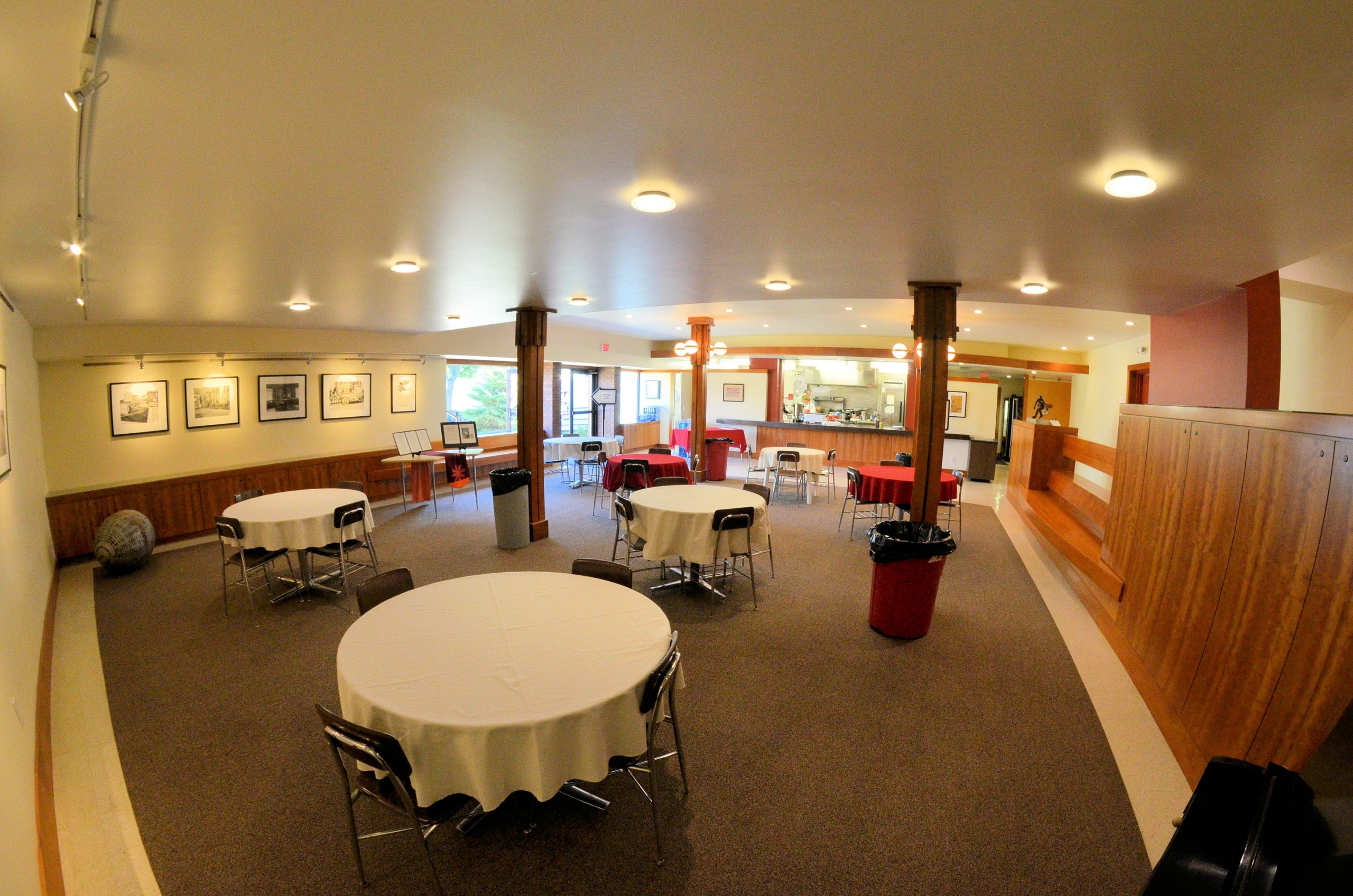 Cafeteria space for rent, linen tablecloths on round tables with cherrywood trim benches and cabinets