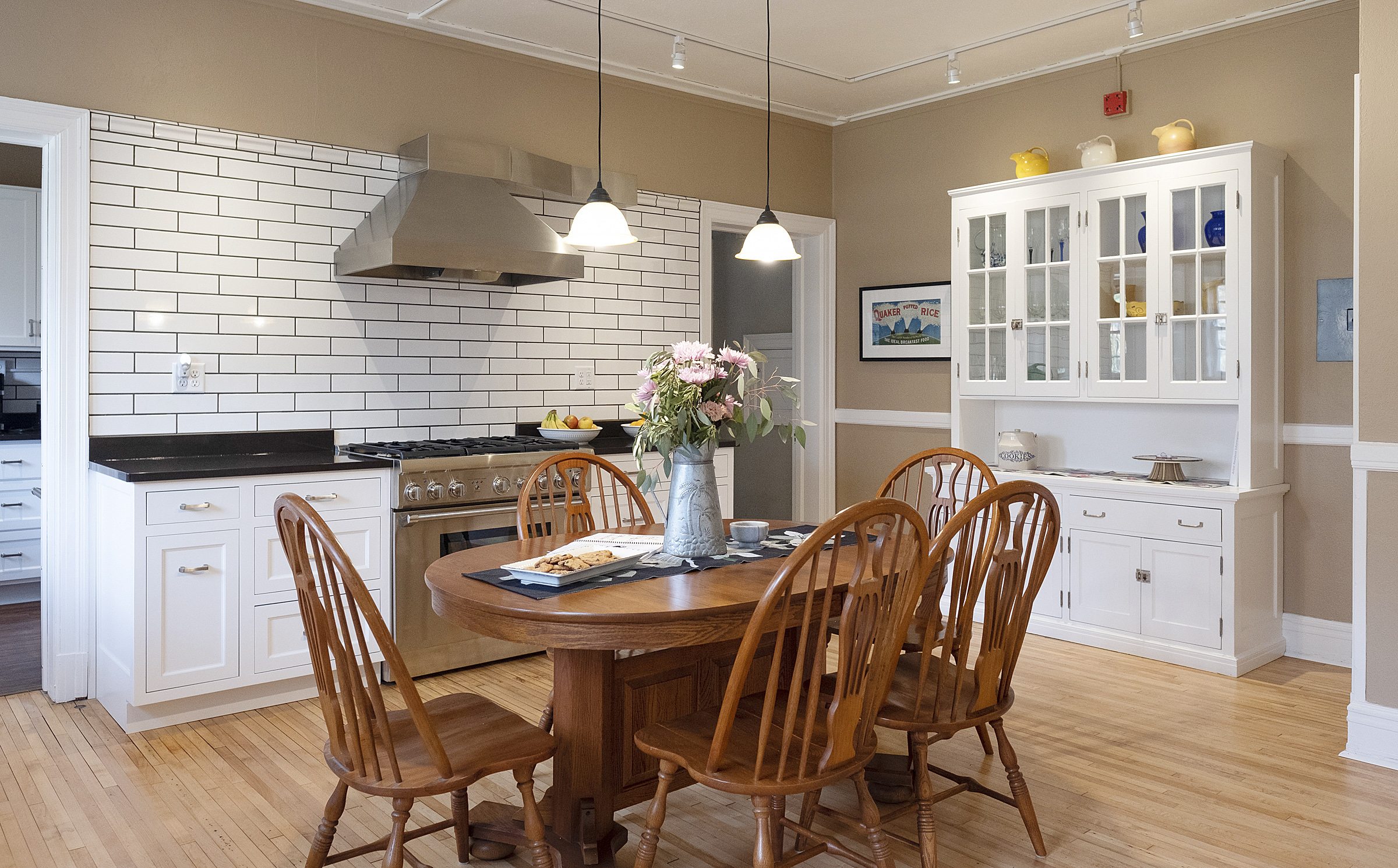 Five chairs around an oak kitchen table with large stainless steel stove and subway tile in the background