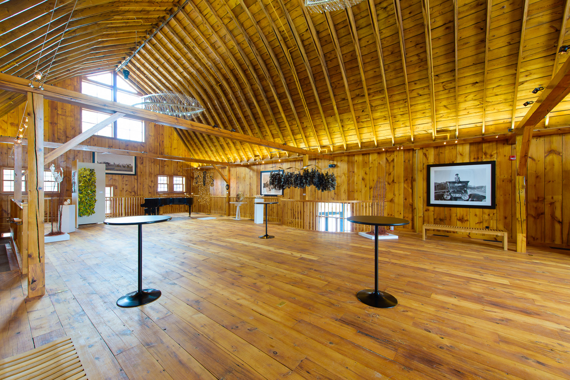 Restored barn available for rent with bar top tables, grand piano and restored, historic photos of A.P. Anderson Family