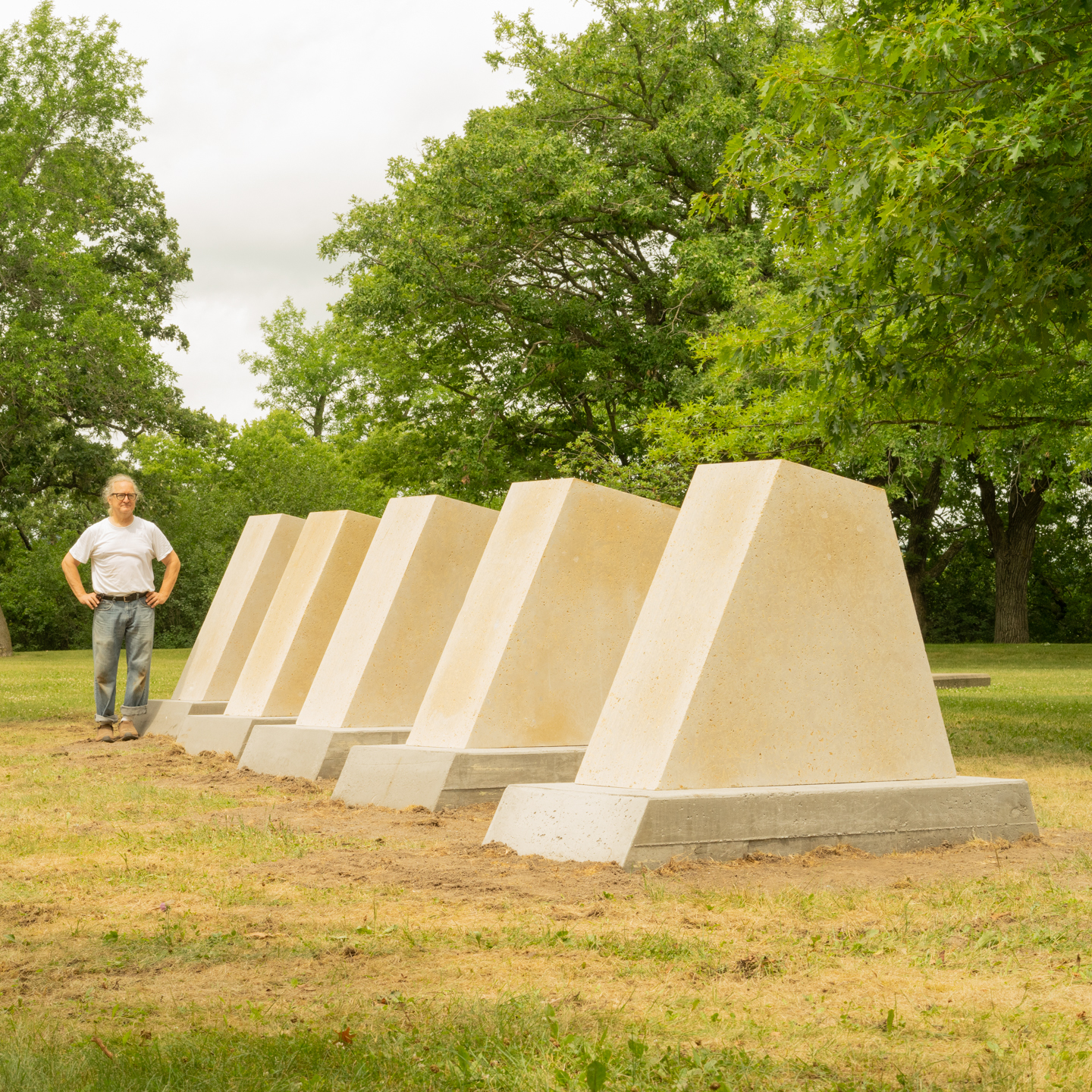 Five large, limestone trapezoids increasing in size in a grassy sculpture garden with trees in background. Sculptor Pete Driessen stands behind his work.